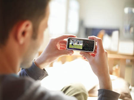 Nokia N77 and a man watching football
